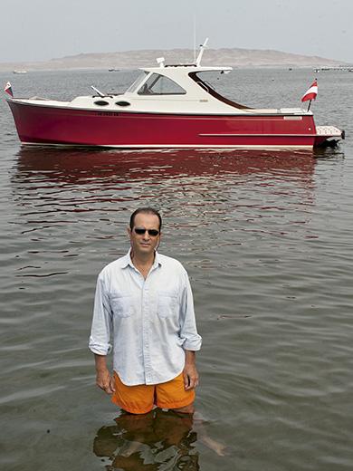 Tony Custer en la bahía de Paracas, frente al bote que él mismo diseñó.