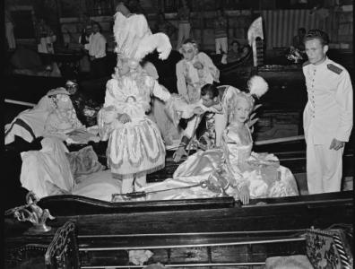 El diseñador de moda francés Jacques Fath y su esposa Genevieve llegan a un baile de disfraces en góndola