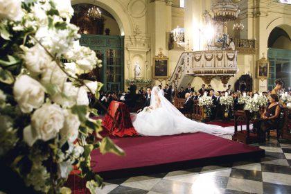 Espléndida decoración floral con velones en las bancas y un estrado especial para la impresionante cola de seis metros de la novia.