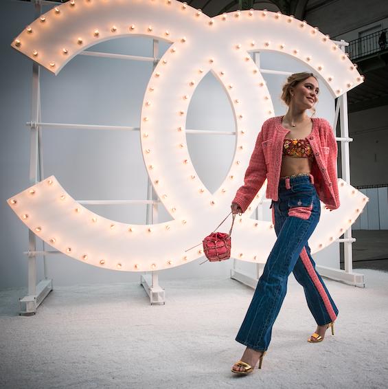 Lily-Rose DEPP, Embajadora CHANEL, llevó una chaqueta de tweed rosado sobre un top bordado de organza y unos jeans, look 9, de la colección Crucero 2021.